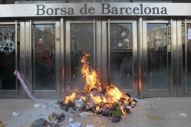 A pile of garbage on fire in front of the Barcelona stock exchange