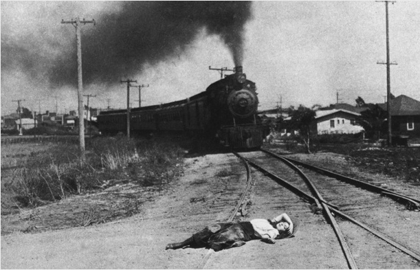 A black and white film still of a woman tied to train tracks as a locomotive approaches